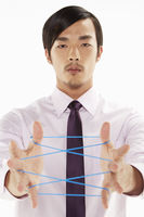 Businessman forming a cat's cradle