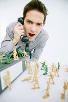 Businessman frowning while talking on the phone, toy soldiers on the table