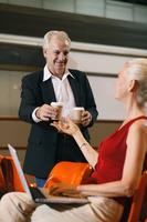 Businessman handing businesswoman a cup of coffee