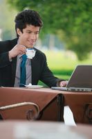 Businessman having tea while using laptop