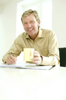 Businessman holding a cup while writing on a book