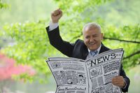 Businessman holding newspaper and raising his hand