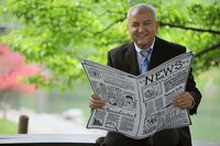 Businessman holding newspaper and smiling