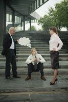 Businessman holding thinking bubble above another businessman's head, businesswoman watching