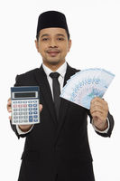Businessman holding up a calculator along with a pile of cash