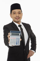 Businessman holding up a calculator
