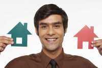 Businessman holding up two cut out houses, smiling
