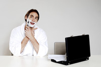 Businessman in bathrobe shaving at his desk