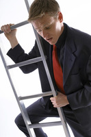 Businessman looking scared climbing up the ladder