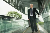 Businessman on escalator, carrying briefcase