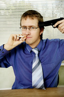 Businessman pointing a pistol at himself while smoking cigarette