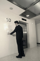 Businessman pushing elevator button