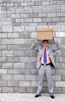 Businessman putting a box on top of his head