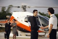 Businessman shaking hands with pilot, businesswomen are walking from helicopter in the background