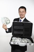 Businessman showing a briefcase of money