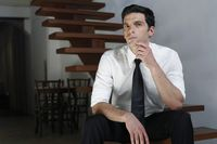 Businessman sitting at the stairs contemplating