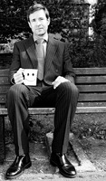 Businessman sitting on the bench holding a cup of coffee