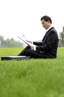 Businessman sitting on the field reading newspaper