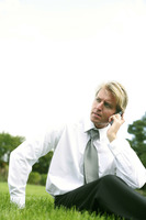 Businessman sitting on the field talking on the phone