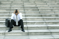 Businessman sitting on the stairs with his hands on the head