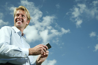Businessman smiling while holding mobile phone