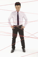 Businessman standing in between tangled wires