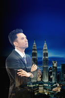 Businessman standing with arms crossed against a cityscape background