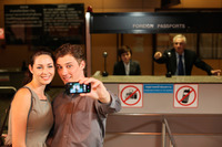 Businessman taking a picture using mobile phone, airline check-in attendant pointing at them
