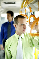 Businessman thinking while standing in a bus