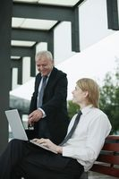 Businessman using laptop, another businessman pointing at the screen