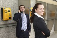 Businessman using public telephone, businesswoman waiting at the side