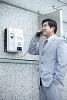 Businessman using the public telephone