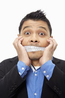 Businessman with a measuring tape wrapped around his mouth