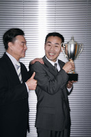 Businessman with a trophy with another businessman congratulating him