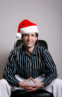 Businessman with christmas hat sitting on the chair smiling