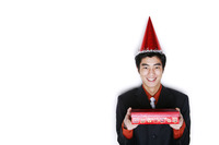 Businessman with party hat holding a gift