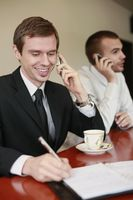 Businessman writing on organizer while talking on the phone