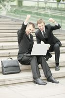 Businessmen looking at laptop and raising fist