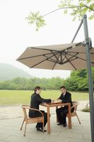 Businessmen playing chess outdoors