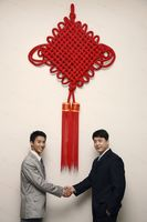 Businessmen shaking hands under a giant chinese new year decoration