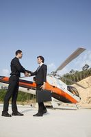 Businessmen shaking hands with helicopter in the background