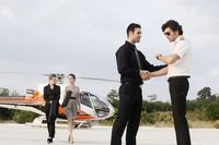 Businessmen shaking hands with pilot while businesswomen are walking away from helicopter