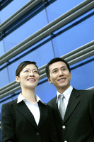 Businesswoman and businessman smiling while looking away