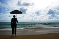Businesswoman holding an umbrella on the beach