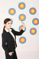 Businesswoman holding darts