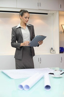 Businesswoman holding pen and clipboard