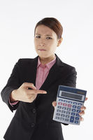 Businesswoman holding up a calculator