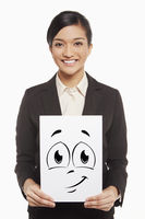 Businesswoman holding up a smiley face doodle