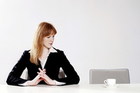Businesswoman looking at a cup of coffee beside her