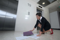 Businesswoman picking up dropped papers